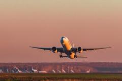 Boeing 777-300er emiratflygbolag tar av på solnedgången Arkivbilder