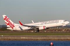 Boeing 737-800 för oskuldAustralien flygbolag som flygplan tar av från Sydney Airport Royaltyfri Foto
