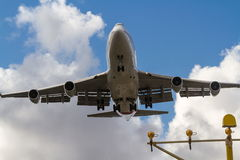 Boeing 747 jumbo jet low overhead. Boeing 747 jet flying low overhead, approaching landing Royalty Free Stock Image