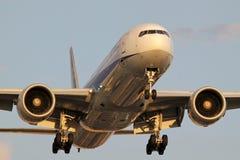 Boeing 777 på kort final på SLAPPT på lågt solljus royaltyfri bild