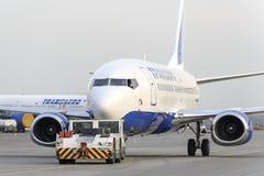 Boeing 737 Transaero aan de baan wordt gesleept die stock fotografie