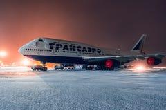 Boeing 747-400 Transaero som parkeras på flygplatsen på natten Arkivbild
