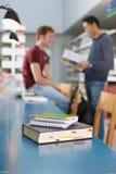 Boek en blocnotes op bureau in bibliotheek Stock Afbeelding