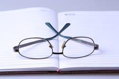 Boek en glazen Stock Foto's