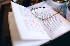Boek en glazen priester` s vrije tijd Stock Foto