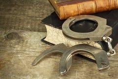 Boek en handcuffs op een houten lijst Het concept straf en rechtvaardigheid Straf voor een misdaad Corruptie en straf stock afbeelding