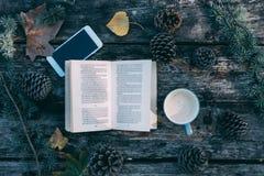 Boek en mobiele telefoon op een houten lijst met koffie en pijnbomenou royalty-vrije stock afbeelding