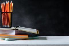 boek en potlood op de witte achtergrond van de lijst zwarte raad met studie stock afbeelding