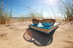 Boek en zonnebril op het strand