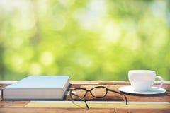 Boek, kop van koffie en oogglazen op een uitstekende houten lijst binnen Royalty-vrije Stock Fotografie