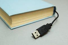 Boek met een schakelaar voor verbinding aan een computer op een grijze achtergrond royalty-vrije stock fotografie