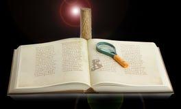 Boek met een vergrootglas en een kaars op een zwarte achtergrond royalty-vrije stock foto