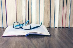 Boek met harde kaftboeken op witte houten lijst, open boek en glazen, exemplaarruimte voor tekst royalty-vrije stock foto
