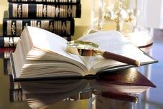 Boek met vergrootglas (lezingsreeks Stock Foto's