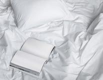 Boek op het slordige bed, creatieve fotosamenstelling met boek en wit bed onder het zonlicht van venster stock afbeeldingen