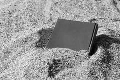 Boek op het zand op een onscherpe die achtergrond, met zand wordt behandeld, in het zwart-wit zand wordt begraven, Royalty-vrije Stock Foto's