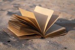 Boek op zand Stock Afbeeldingen