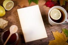 Boek, thee en honing op lijst met de herfstbladeren Royalty-vrije Stock Foto