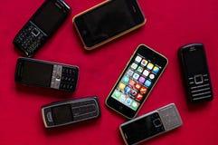 BOEKAREST, ROEMENIË - MAART 17, 2014: Foto van iphone tegenover oude Nokia-telefoons op een rode achtergrond die de evolutie van  royalty-vrije stock afbeelding