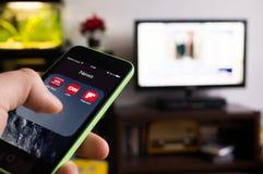 BOEKAREST, ROEMENIË - NOVEMBER 21, 2014: Foto van hand die een iphone met nieuws apps op het scherm en TV-reeks op de achtergrond Royalty-vrije Stock Afbeelding