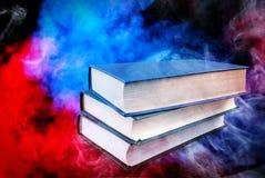 Boeken bovenop elkaar en een kleurrijke achtergrond worden gestapeld die stock foto's