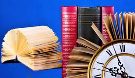 Boeken in de bibliotheek op de lijst en een uitstekende klok Het boek is het literair, wetenschappelijk werk, een bron van kennis stock afbeeldingen