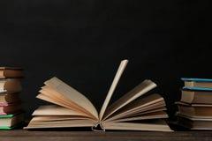 Boeken en geopend boek op een bruine houten lijst en op een zwarte achtergrond Oude Boeken Onderwijs school studie stock fotografie
