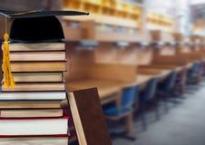 Boeken en graduatiehoed in onderwijsbibliotheek royalty-vrije stock foto