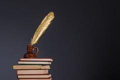 Boeken en inktpot met gouden ganzepen op bovenkant Stock Fotografie