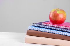 Boeken en oefenboeken met een appel op een witte lijst en op een grijze achtergrond De levering van de school stock foto