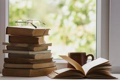 Boeken, koppen, glazen op het venster Stock Afbeelding
