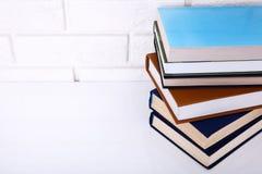 Boeken op de lijst dichtbij bakstenen muur Exemplaar ruimte en selectieve nadruk Macro Royalty-vrije Stock Fotografie