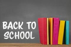 Boeken op de lijst tegen grijs bord met terug naar schooltekst Stock Foto's