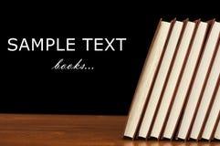Boeken op een houten lijst aangaande een zwarte Stock Foto