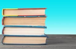 Boeken op een lijst aangaande een groene achtergrond stock afbeeldingen