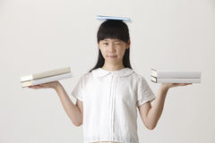 Boeken op haar hoofd stock afbeelding