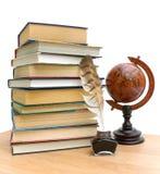 Boeken, pen, inkt en uitstekende bol op witte achtergrond Stock Foto's
