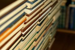 Boeken in stevige overstroming op de achtergrond van een boekenrekclose-up stock afbeeldingen