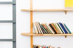 Boekenrek met boeken in een wit ontworpen binnenland Stock Foto