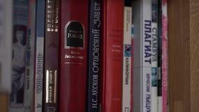 boekenrek Oude boeken op een houten plank Vele oude boeken op boekenrek in bibliotheek stock footage