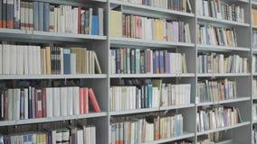 Boekenrekken in universitaire bibliotheek met veel boeken stock footage