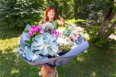 Boeket als gift Het roodharige meisje ontvangt bloemen als gift A royalty-vrije stock foto's