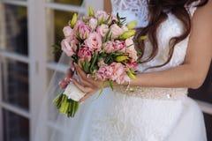Boeket in de handen van de mooie bruid bij huwelijksdag royalty-vrije stock fotografie