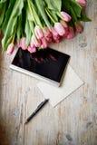 Boeket die van tulpen op een houten oppervlakte, dicht bij de tablet, de pen en het document liggen Stock Afbeeldingen