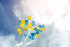 Boeket van blauwe en gele ballons in de hemel Stock Afbeeldingen
