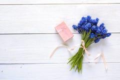 Boeket van blauwe muscaribloemen met giftdoos op witte houten bedelaars Royalty-vrije Stock Afbeeldingen