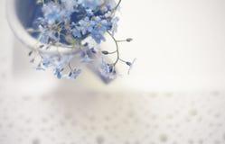 Boeket van blauwe vergeet-mij-nietjes in een kop op een kanten dienblad, de hoogste mening Royalty-vrije Stock Fotografie