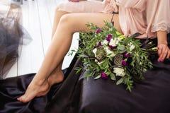 Boeket van bloemen dichtbij de zittingsvrouw in een peignoir Royalty-vrije Stock Foto's