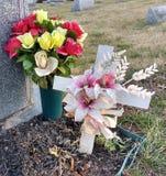 Boeket van Bloemen en Wit Kruis in een Begraafplaats Stock Foto