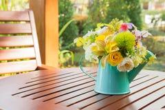 Boeket van bloemen in gieter op houten lijst stock foto